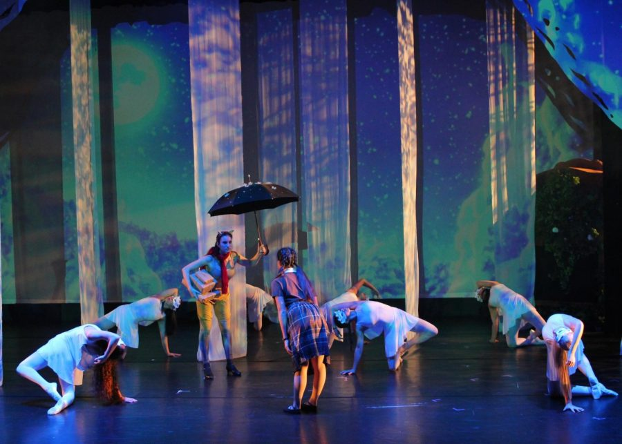 Lucy Pensive, performed by Jamie Xiao (20) greets Mr. Tummus the faun, performed by Maya Minagawa (20). An ensemble of snowflakes (Delilah Delgado (21), Cami Farrell (22), Ashlyn Hinter (22), Jess Li (20), Sheridan Spain (20), Elise Watson (22) and Sharisa You (22)) surrounds them.