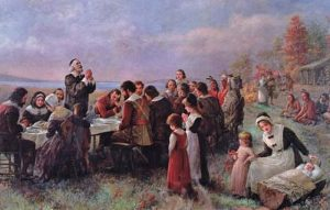 """The First Thanksgiving at Plymouth"" by Jennie Augusta Brownscombe, painted in 1914, depicts the Pilgrims and the Wampanoag people gathering around a table full of food from their harvest for the first Thanksgiving dinner."